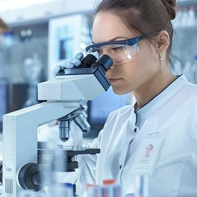 Medical Research Scientists Looking at Samples Under Microscope. She Works in a Bright Modern Laboratory.